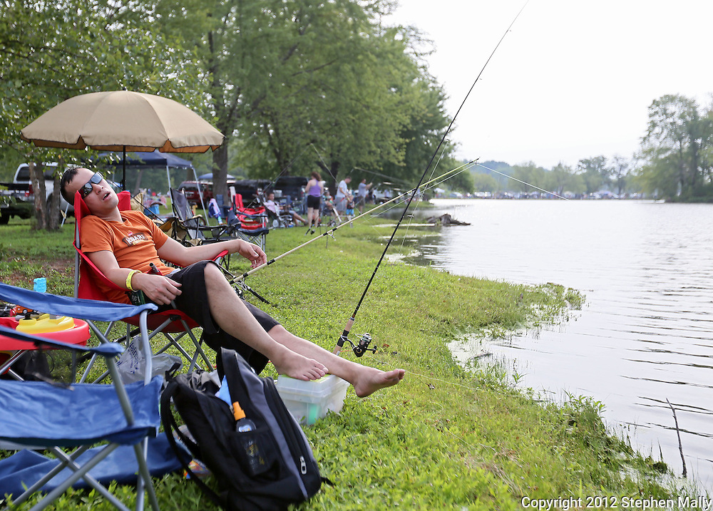 Zach Schmelzer, of Cedar Rapids, sleeps while his lines are in the water during the 10th annual Boys & Girls Clubs of Cedar Rapids Fish-O-Rama at Robbins Lake in Cedar Rapids on Saturday, August 4, 2012. Organizers expected 1,200-1,500 participants in the weekend event. There were 426 prizes available to people who caught tagged fish. Prizes included a Toyota truck, boat, TVs, grills, bicycles, and gift certificates.