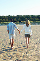 Couple Walking on Beach holding hands back view