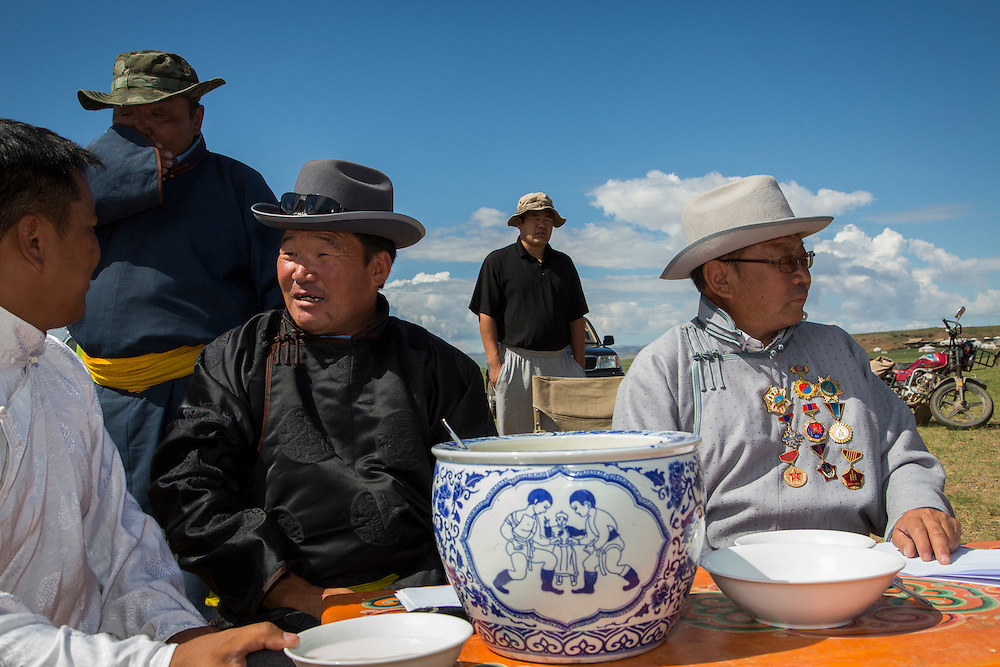 A judge for the upcoming Naadam Festival sits behind a table with a pot of mare's milk on it, wearing Mongolian Deel - the traditional Mongolian men's attire and medals from his time spent in the Mongolian Boarder Guard at the Three Camel Lodge in the Gobi Desert of Mongolia on July 31, 2012. © 2012 Tom Turner Photography.