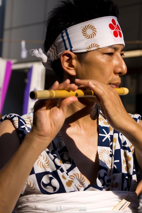 A man playing a flute in the Tenjin Festival (Tenjin Matsuri) in Osaka.