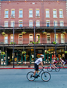 Stock photography of a biker riding past the New Orleans hotel in downtown Eureka Springs, Arkansas.