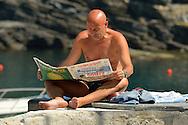 Vacationer reading newspaper in Vernazza, Cinque Terre, Liguria, Italian Riviera, Italy, Europe