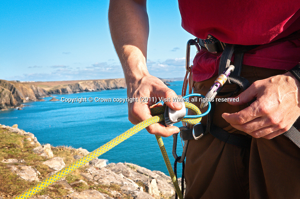 Climber kitting up<br /> Rock climbing<br /> Carreg y Barcud<br /> Near St David's<br /> Pembrokeshire<br /> South<br /> Activities and Sports
