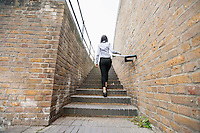 Rear view of young businesswoman walking up stairs