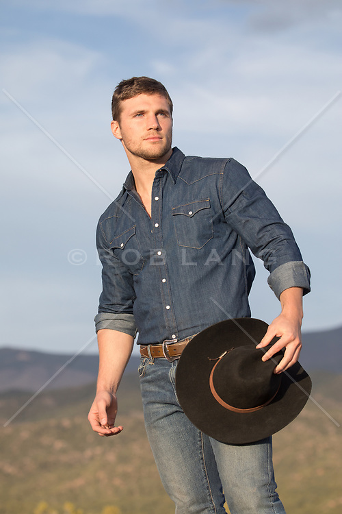cowboy holding his cowboy hat outdoors