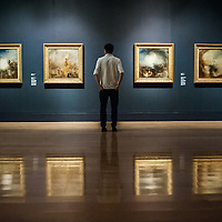 London, UK - 8 September 2014: a gallery assistant looks up at works from the 1840s by J.M.W. Turner