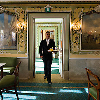 VENICE, ITALY - DECEMBER 02:  A waiter of the Caffe Quadri enters one of the main rooms on December 2, 2011 in Venice, Italy.The Venetian coffee houses have a  long standing history, established at the beginning of 1700 around St. Mark Square have been the centre of cultural meeting and innovations for centuries and served customers like Dickens, Goethe, Casanova and Lord Byron. San Marco is one of the six sestieri of Venice, lying in the heart of the city.