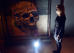 "© Licensed to London News Pictures. 14/11/2012. London, UK A woman stands with ""Calavera"" a plasticine three dimensional piece made by Argentinian collective Mondongo. Press preview of ""Death: A Self -Portrait. The Richard harris Collection"" at The Welcome Collection today 14th November 2012. The exhibition showcases 300 works from a unique collection devote to the iconography of death and mankind's attitude towards it. Photo credit : Stephen Simpson/LNP"