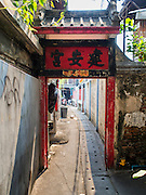 11 FEBRUARY 2015 - BANGKOK, THAILAND:  An alley leading to the Kuan An Keng Chinese shrine next to the Santa Cruz community in the Thonburi section of Bangkok. The shrine was first built during the reign of King Taksin the Great (ca 1767) but was renovated during the reign of Rama III, in the early 1800s. The Santa Cruz neighborhood is a Catholic enclave next to the shrine. The neighborhood is known for the Thai adaptation of Portuguese cakes baked in the neighborhood. Several hundred Siamese (Thai) Buddhists converted to Catholicism in the 1770s. Some of the families started baking the cakes. When the Siamese Empire in Ayutthaya was sacked by the Burmese, the Portuguese and Thai Catholics fled to Thonburi, in what is now Bangkok. The Portuguese established a Catholic church near the new Siamese capital. There are still a large number of Thai Catholics living in the neighborhood around the church.         PHOTO BY JACK KURTZ