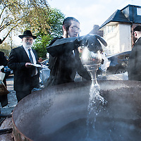 London, UK - 9 April 2014: members of the Jewish community of Stamford Hill bring cutlery, pots, pans and dishes to kosher in boiling water in preparation for Passover. According to the Torah, as it is forbidden to eat chametz (leavened food) during Passover, utensils which have come into contact with chametz, can be immersed in boiling water (hagalat keilim) to purge them of any traces of chametz that may have accumulated during the year.