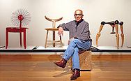 Furniture maker Sam Maloof sits among some of the chairs in the show he is curator of, at the Worcester Center for Crafts.