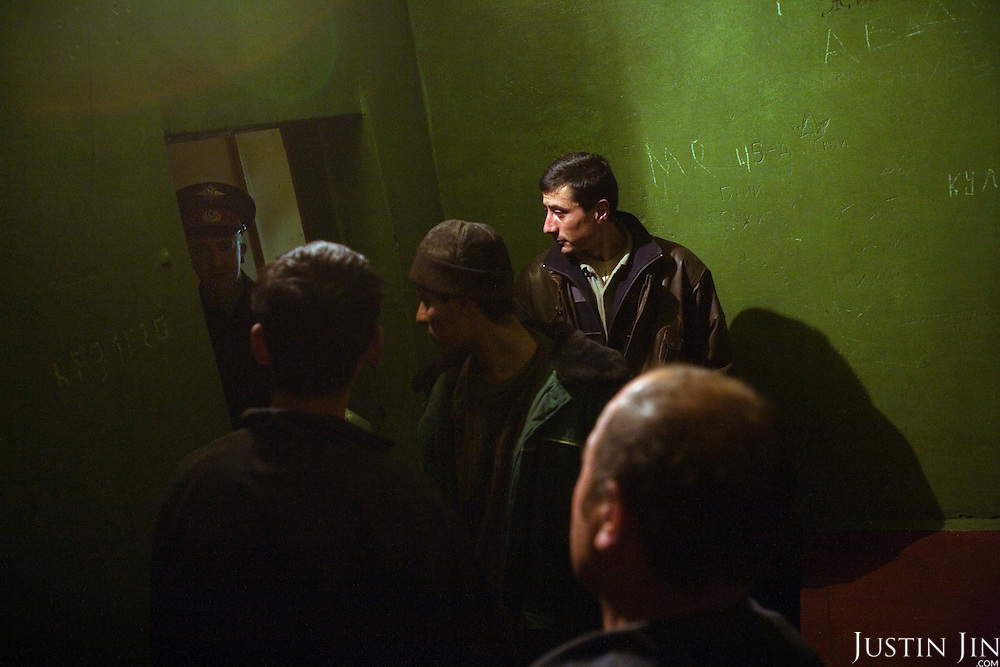 A policeman locks up four Tajik workers in a prison cell after they were arrested for working without a permit in Moscow. Russia is cracking down on foreign nationals working in its markets and construction sites.