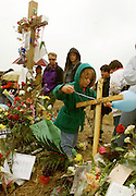 DEN107D:CRIME-SHOOTING:LITTLETON,COLORADO,01MAY99 - Hayley Gardiner ties a blue balloon to a tiny cross for Erik Harris, one of the killers in the Columbine High School shootings May 1. The father of one of the students killed by Harris destroyed the cross erected for him but another much smaller one appeared later. Hundreds waited in the rain to pay respects at a memorial to those killed in the Columbine High School shootings.  rtw/Photo by Rick Wilking