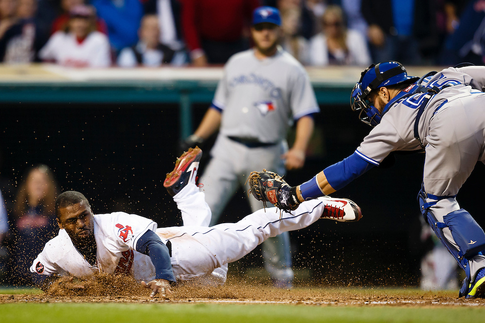 May 1, 2015; Cleveland, OH, USA; Cleveland Indians center fielder Michael Bourn (24) dives into home and is tagged out by Toronto Blue Jays catcher Russell Martin (55) in the fourth inning at Progressive Field. Bourn was called safe on the field but the call was overturned on replay challenge. Mandatory Credit: Rick Osentoski-USA TODAY Sports