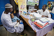 Diallo Amadou, 25, holds his son Diallo Mamadou Kalidou, 9 months, who suffers from anemia and malaria, as they meet with a nurse during a consultation at the Libreville health center in Man, Cote d'Ivoire on Wednesday July 24, 2013.