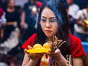 "08 FEBRUARY 2016 - BANGKOK, THAILAND: A woman prays in front of a small Chinese shrine in Bangkok's Chinatown district during the celebration of the Lunar New Year. Chinese New Year is also called Lunar New Year or Tet (in Vietnamese communities). This year is the ""Year of the Monkey."" Thailand has the largest overseas Chinese population in the world; about 14 percent of Thais are of Chinese ancestry and some Chinese holidays, especially Chinese New Year, are widely celebrated in Thailand.       PHOTO BY JACK KURTZ"