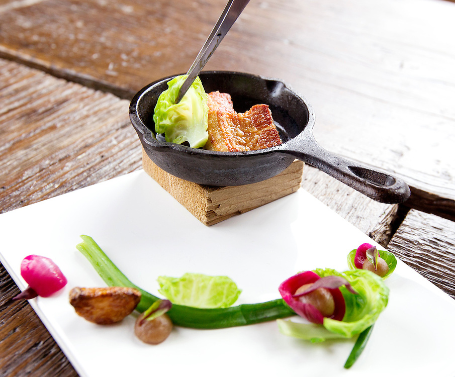 Pork belly cooks in a tiny skillet on the table with greens, garlic, Brussels sprout, and date purée at Travail and the Rookery in Robbinsdale April 18, 2014.