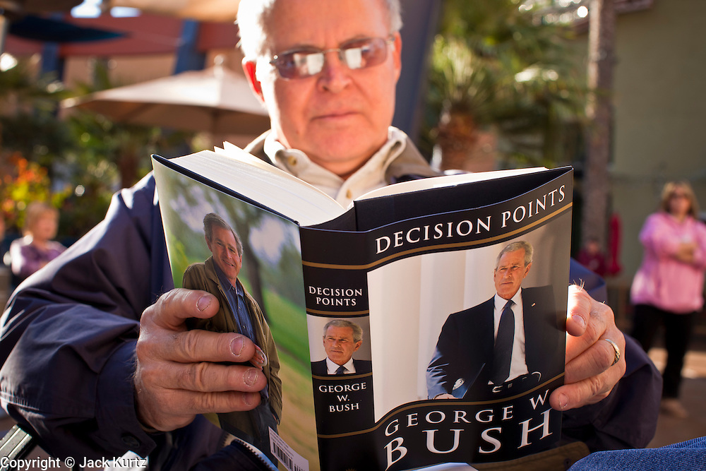 "09 DECEMBER 2010 - PHOENIX, AZ: PAUL TELLEZ, from Phoenix, reads George W. Bush's book, ""Decision Points"" after waiting for more than five hours to get an autographed copy at the Barnes & Noble Bookstore in Phoenix, AZ, Thursday, Dec. 9. More than 2,000 people lined up starting at 5AM to get copies of the former President's book, ""Decision Points."" A handful of protesters demonstrated against President Bush near the bookstore, calling him a ""war criminal.""   PHOTO BY JACK KURTZ"