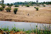Vietnamese dams along the Sesan River, in the Mekong Delta, affect the lives ethnic minority villages downstream, in Andong Meas District, in Ratanakiri Province, Cambodia, Wednesday, May 5, 2010. A man walks along a dry river bed portion of the Sesan River, near Andong Meas.