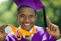 Graduate with medal holding one finger up outside portrait