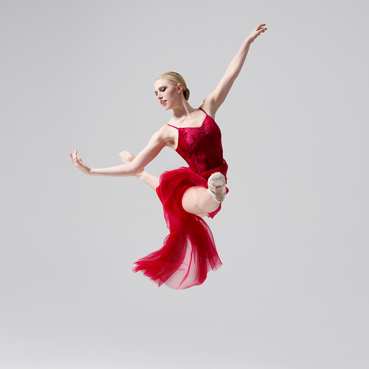 Contemporary ballet female dancer in a red dress, Laura Anne Wallace, in a jete jump, taken in the photo studio on a light gray background. Photograph taken in New York City by photographer Rachel Neville.