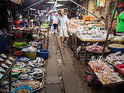 13 MAY 2015 - SAMUT SONGKRAM, SAMUT SONGKRAM, THAILAND:   A man walks through the market in Samut Songkram. The market is next to the railroad tracks. When a train comes in the vendors move their shops off the tracks. It has become a major tourist attraction in the town.    PHOTO BY JACK KURTZ