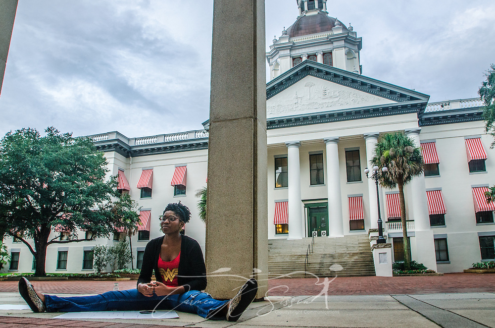 "LaQuinta Alexander, 21, sits outside the Florida state capitol in Tallahassee, Fla., on July 20, 2013, in support of Dream Defenders, a youth-led activist group which sequestered itself within the building July 16, 2013, demanding a special legislative session to address concerns over racial profiling and Florida's ""stand-your-ground"" self-defense law. The group formed in 2012 after the fatal shooting of 17-year-old Trayvon Martin.  (Photo by Carmen K. Sisson/Cloudybright)"