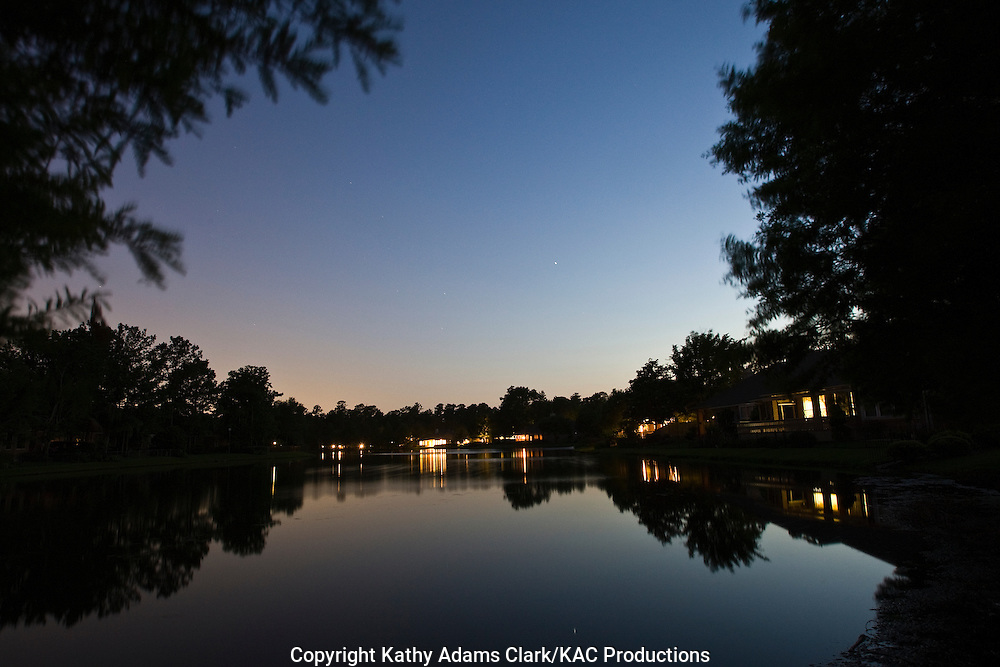 Residential, neighborhood pond, at twilight with lights on the houses, The woodlands, Texas.
