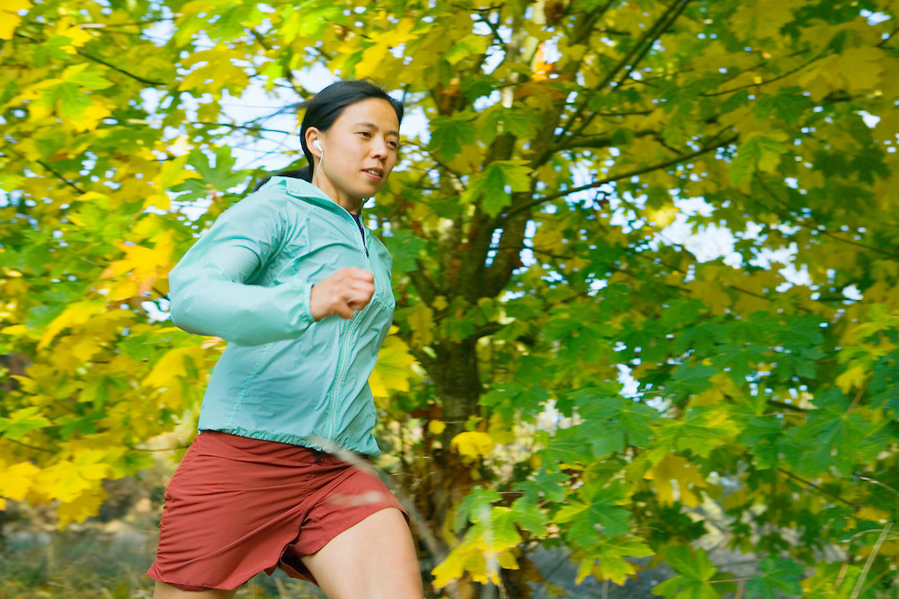Low angle young Asian woman running with MP3 player.
