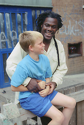 Boy and carer playing outside entrance to block of flats,