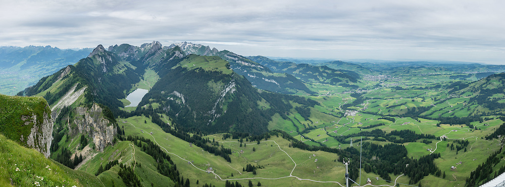 View down to Sämtisersee lake from Hoher Kasten mountain in the Alpstein limestone range, Appenzell Alps, overlooking the Rhine in Eastern Switzerland, Europe. In the valley on right, see Brülisau, Weissbad, Schwende, Steinegg and Appenzell villages. Hoher Kasten (1795 m) is on the border between the cantons of Appenzell Innerrhoden and St. Gallen. Appenzell Innerrhoden is Switzerland's most traditional and smallest-population canton (second smallest by area). This image was stitched from multiple overlapping photos.