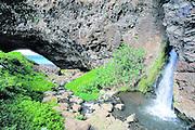 Waterfall and arch, Honopu Beach, Napali Coast, Kauai, Hawaii