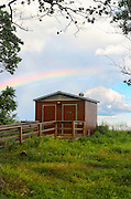 Eco friendly green outhouse on Sheffield Island Norwalk Connecticut with rainbow, August 2013. The composting toilets require no energy or plumbing and the ramp makes them handicapped accessible. There is no electricity on the island and it is only accessible via ferry or other boat.
