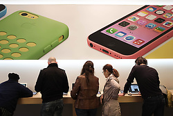 © Licensed to London News Pictures. 27/10/2013. London, UK. Shoppers use Apple products beneath instore images of the Apple iPhone 5C  at Apple's UK flagship Regent Street store.  Apple is to announce its Q4 Fiscal Results tomorrow - the company launched the iPhone 5C in the closing weeks of the quarter to as a lower cost option in an effort to attract budget users.  Photo credit : Richard Isaac/LNP