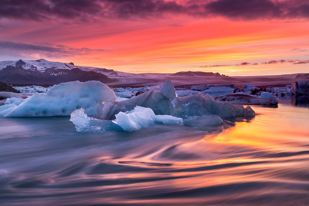 A wide angle landscape of icebergs floating in the Jokulsarlon glacial lagoon in Iceland with a colorful sunset sky