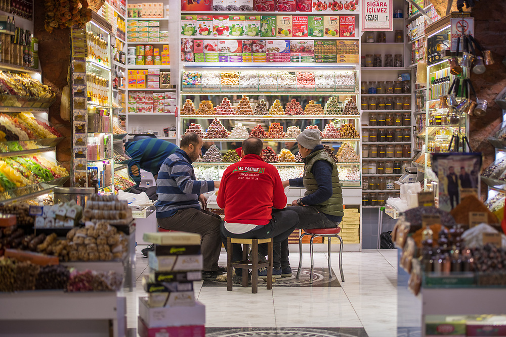 Group of men gather and sit around small table in sweet shop at Istanbul Spice bazaar in Turkey