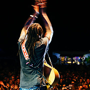 Micahel Franti and Spearhead perform to a packed crowd in Teton Village, Wyoming. Close-up of Michael Franti performing with guitar.
