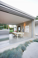 Glass wall of open plan dining / kitchen area in Palm Springs home