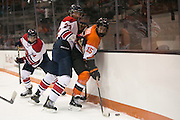RIT's Max Mikowski and Brock University's Daniel Tanel fight for a puck in the corner during a game at the Gene Polisseni Center on Saturday, October 4, 2014.