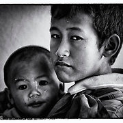 An ethnic Karen refugee and his younger brother wait to beg money from others in Mae Sot, Thailand.  (Photo by David Longstreath)