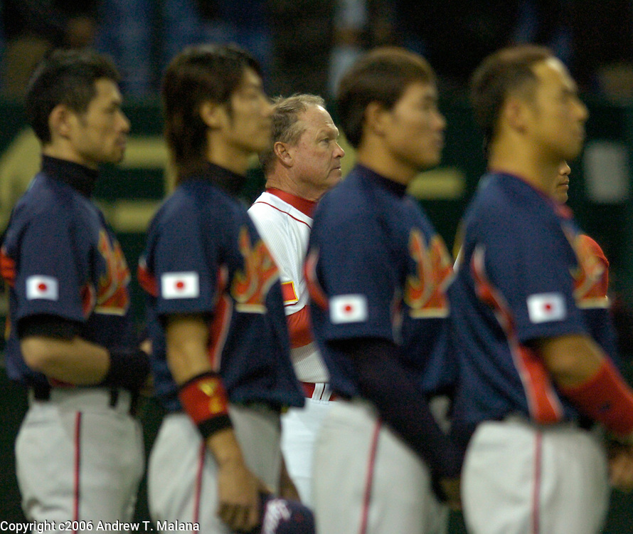 Team China manager Jim Lefebvre in the white jersey stands behind Team Japan during the playing of the Chinese National Anthem before the start of the second game of the World Baseball Classic at Tokyo Dome, Tokyo, Japan.