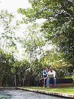Two men sitting in garden using laptop