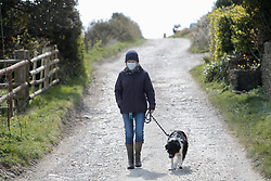 Covid 19 - Woman wearing a face mask while outdoors dog walking. Dorset UK March 2020. Posed by model
