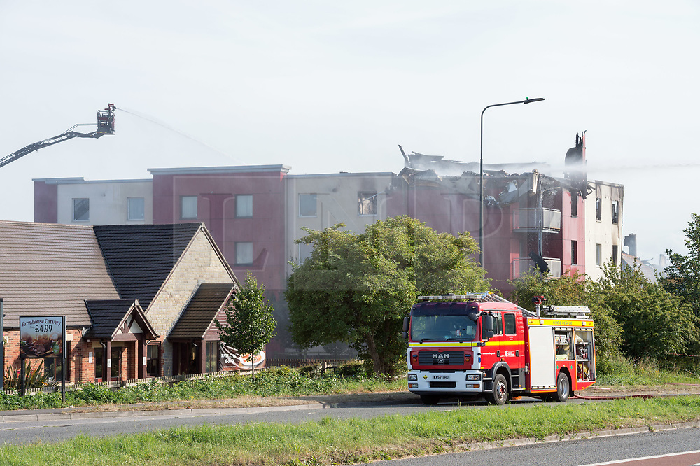 © Licensed to London News Pictures. 18/07/2019; Bristol, UK. Avon Fire and Rescue and the Emergency Services have spent 24 hours tackling a fire at the Premier Inn on Lysander Road in Cribbs Causeway near Bristol. The fire has destroyed the hotel roof, and parts of the hotel have fallen onto the A4018 Cribbs Causeway dual carriageway which has led to the road being completely closed. Photo credit: Simon Chapman/LNP.