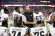 Oakland Raiders offensive line coach Mike Tice points out some play formations on an electronic tablet to a group of offensive linemen on the sideline during pregame warmups before the 2016 NFL preseason football game against the Arizona Cardinals on Friday, Aug. 12, 2016 in Glendale, Ariz. The Raiders won the game 31-10. (©Paul Anthony Spinelli)