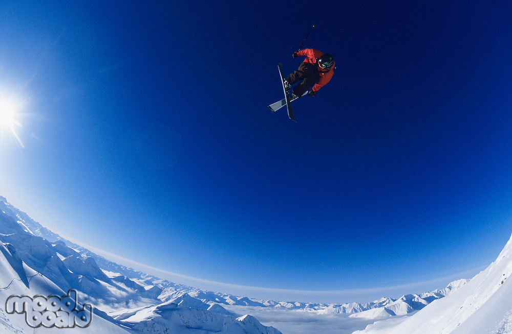 Skier jumping against blue sky