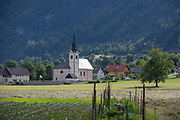 A rural Slovenian church and a local woman tending crops, on 18th June 2018, in Bohinjska Bela, Bled, Slovenia.