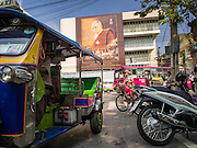 12 DECEMBER 2013 - BANGKOK, THAILAND: Traffic goes past a large portrait of Somdet Phra Nyanasamvara, the Supreme Patriarch of Thailand in front of Wat Bowon Niwet in Bangkok. Somdet Phra Nyanasamvara, who headed Thailand's order of Buddhist monks for more than two decades and was known as the Supreme Patriarch, died Oct. 24 at a hospital in Bangkok. He was 100. He was ordained as a Buddhist monk in 1933 and rose through the monastic ranks to become the Supreme Patriarch in 1989. He was the spiritual advisor to Bhumibol Adulyadej, the King of Thailand when the King served as monk in 1956. There is a 100 day mourning period for the Patriarch, the service Thursday, on the 50th day, included members of the Thai Royal Family. Although the Patriarch was a Theravada Buddhist, he was the Supreme Patriarch of all Buddhists in Thailand, including the Mahayana sect, which is based in Chinese Buddhism.     PHOTO BY JACK KURTZ