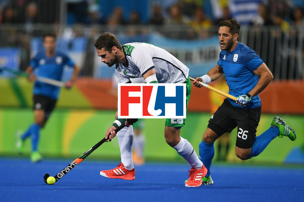 Ireland's Paul Gleghorne and Argentina's Agustin Mazzilli (R) vie during the mens's field hockey Ireland vs Argentina match of the Rio 2016 Olympics Games at the Olympic Hockey Centre in Rio de Janeiro on August, 12 2016. / AFP / MANAN VATSYAYANA        (Photo credit should read MANAN VATSYAYANA/AFP/Getty Images)