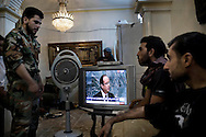 SYRIA, ALEPPO : Rebels from the Free Syrian Army follow international news in a flat turned into military post on September 26,2012. ALESSIO ROMENZI